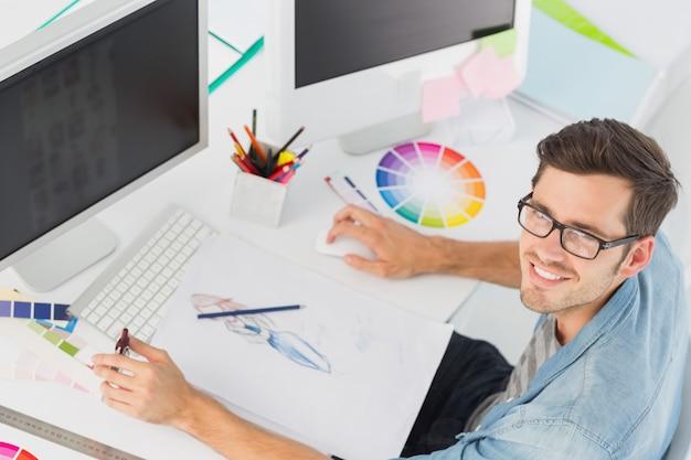 Éditeur de photos masculin occasionnel utilisant un ordinateur