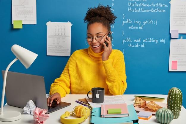 Un éditeur web professionnel crée la structure technique du site web, discute de certains problèmes de travail via un smartphone, porte des lunettes, surfe sur internet sur un ordinateur portable moderne.
