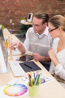 Éditeurs de photo occasionnels concentrés utilisant l'ordinateur au bureau
