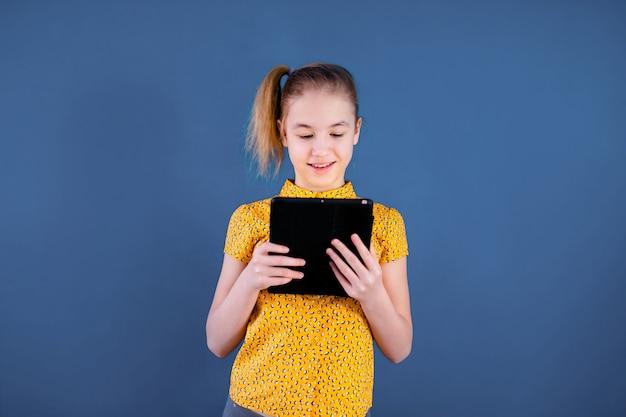 Éducation, école, technologie et concept internet - petite fille étudiante avec tablette à l'école