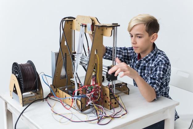 Éducation, enfants, concept technologique - garçon adolescent imprime sur une imprimante 3d.