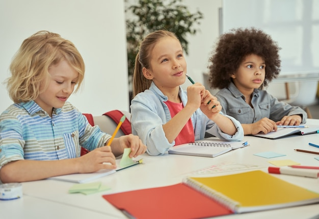 L'éducation est la clé de beaux enfants diversifiés qui étudient et prennent des notes tout en étant assis ensemble à la table