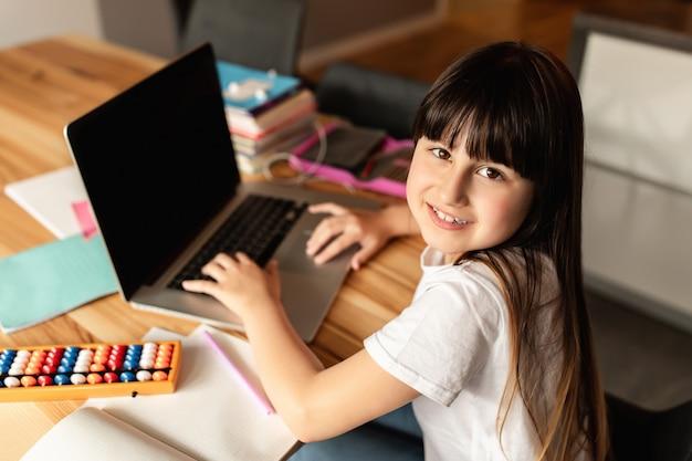 Éducation en ligne. fille heureuse avec ordinateur portable et livres à la maison. apprentissage en ligne, système d'apprentissage en ligne