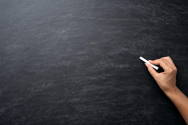 L'éducation ou la rentrée scolaire concept. main tenant la craie sur le tableau.