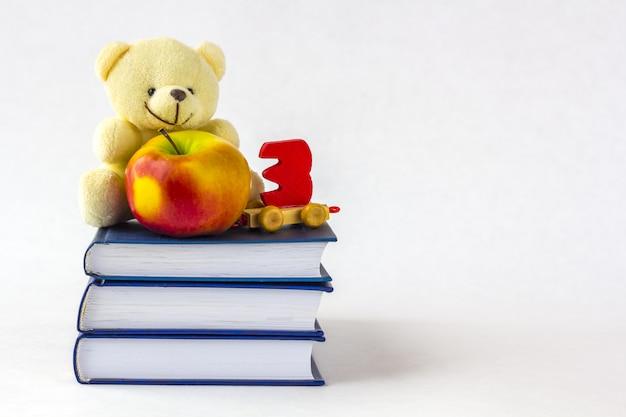 L'éducation ou la rentrée scolaire. une pomme et un ourson et un jouet en bois en forme de nombre sur une pile de livres sur un fond blanc