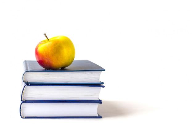 L'éducation ou la rentrée scolaire. une pomme sur une pile de livres isolée sur un blanc avec la surface.