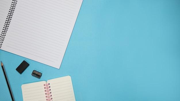 Éducation ou retour à l'école concept. vue de dessus des fournitures scolaires colorées avec des livres, des crayons de couleur, une calculatrice, des pinces à stylo et une pomme sur fond bleu pastel. mise à plat.