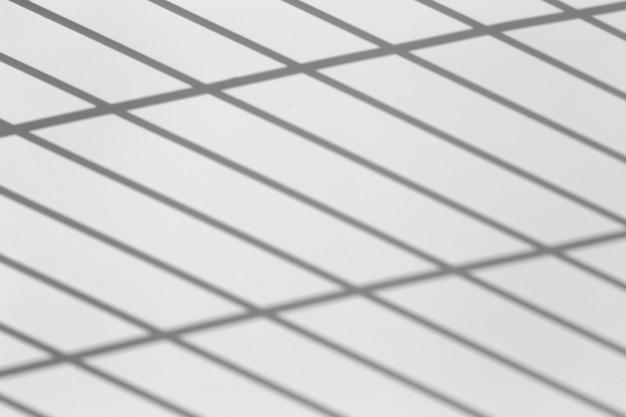 Effet de superposition d'ombre. ombres provenant de lignes de quadrillage ou de grillage d'une clôture ou d'un garde-corps sur un mur blanc propre par temps clair et ensoleillé. ombres géométriques