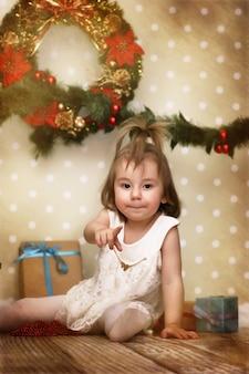 Effet vintage sur photo jolie petite fille habille l'arbre de noël sur le sol dans la chambre