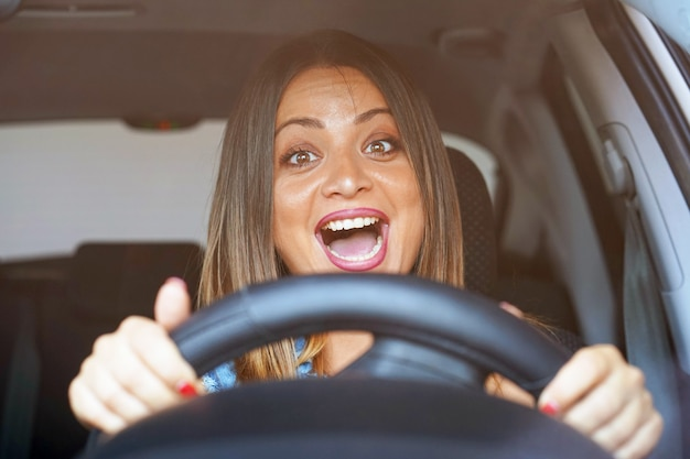Effrayé, figure, femme, conduite, voiture closeup portrait mécontent en colère énervé agressive femme au volant de voiture.