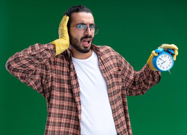 Effrayé jeune beau mec de nettoyage portant un t-shirt et des gants tenant un réveil mettant la main sur la joue isolé sur un mur vert
