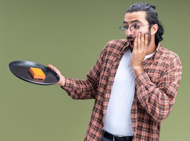 Effrayé jeune beau mec de nettoyage portant t-shirt tenant et regardant une éponge sur le plateau mettant la main sur la joue isolé sur mur vert olive