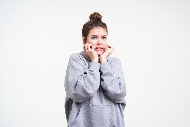 Effrayé jeune femme aux cheveux bruns aux yeux bleus tenant son visage avec les mains levées tout en regardant avec effroi à la caméra, isolé sur fond blanc en sweat à capuche gris