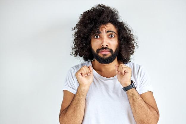 Effrayé jeune homme arabe bouclé se tenir dans la peur par quelque chose, regarder la caméra