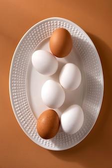Egges de poulet brun et blanc sur fond beige.