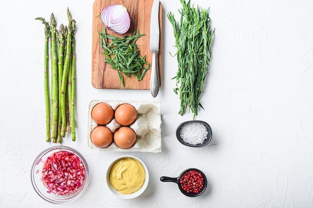 Eggsufs d'asperges et ingrédients de la vinaigrette française avec moutarde de dijon, oignon haché dans du vinaigre rouge à l'estragon sur fond texturé blanc, vue de dessus.