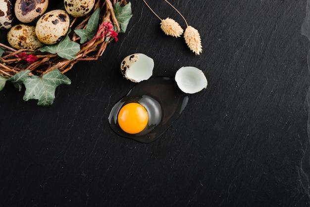 Eggsufs de caille sur fond de pierre noire, œuf de caille cassé et fêlé, jaune d'œuf de caille. produit biologique.