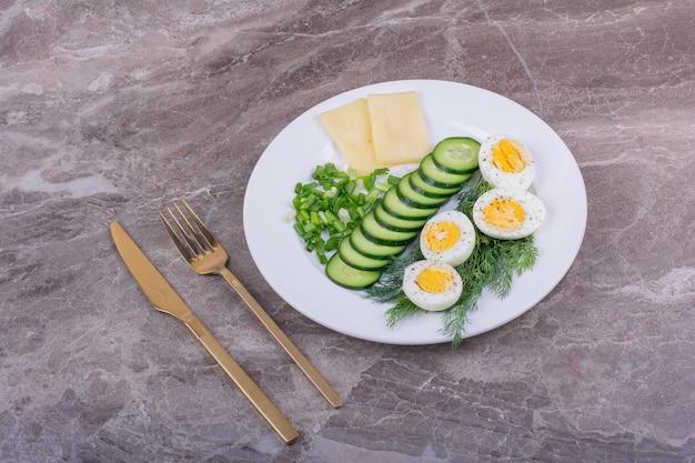 Eggsufs durs avec des tranches de concombres et d'herbes dans une assiette blanche.