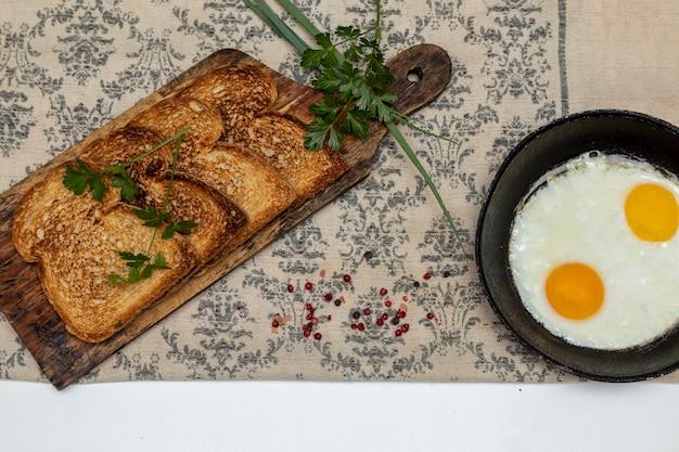 Eggsufs frits dans une poêle en fer rustique, toasts sur une planche en bois et une tasse de café pour le petit-déjeuner. vue de dessus