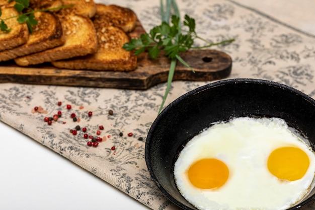 Eggsufs frits dans une poêle en fer rustique, toasts sur une planche en bois et une tasse de café pour le petit-déjeuner.