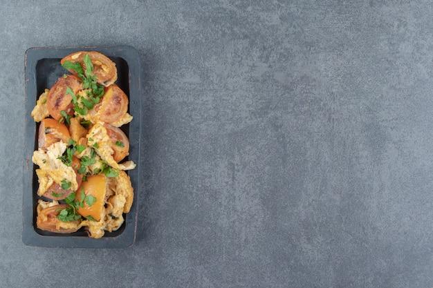 Eggsufs frits à la tomate sur plaque noire.