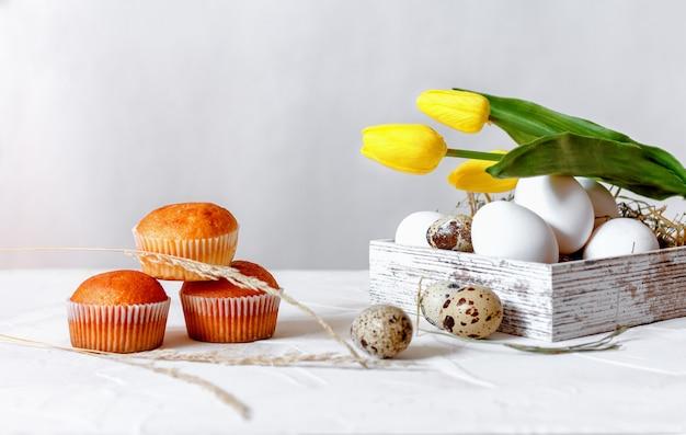 Eggsufs de poule blancs et œufs de caille dans une boîte en bois avec de la paille sur fond clair.