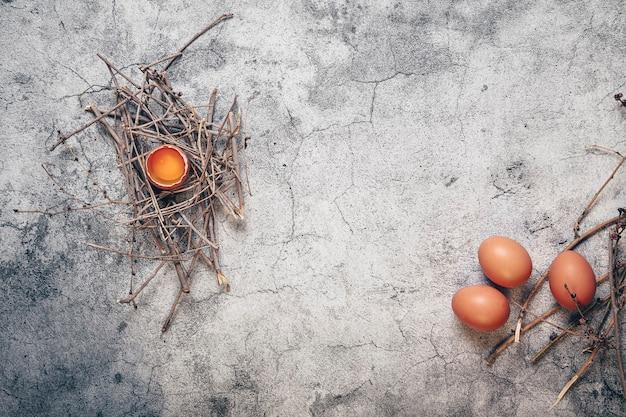 Egguf cassé sur nid et autres sur le côté, œufs frais sur pierre