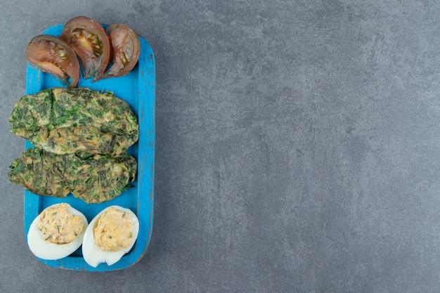 Egguf à la coque et œuf au plat avec des verts sur plaque bleue.
