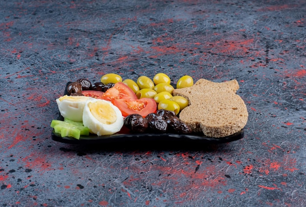 Egguf à la coque avec olives et tomates marinées noires et vertes.