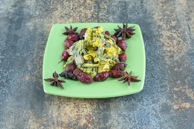 Églantier séché et fleurs sur plaque verte.