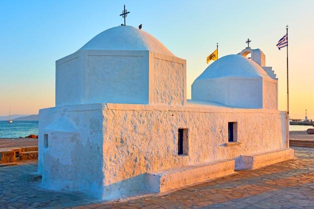 Église d'agios nikolaos dans le port de l'île d'égine au coucher du soleil, grèce