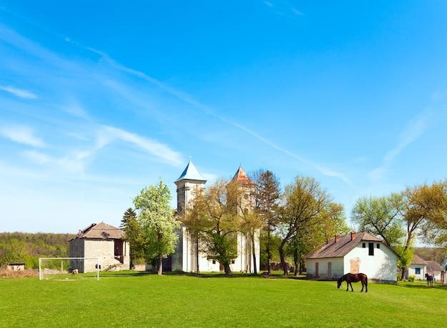 Église de l'annonciation de la bienheureuse vierge marie (village de sydoriv, région de ternopil, ukraine, construite en 1726-1730) et terrain de football.