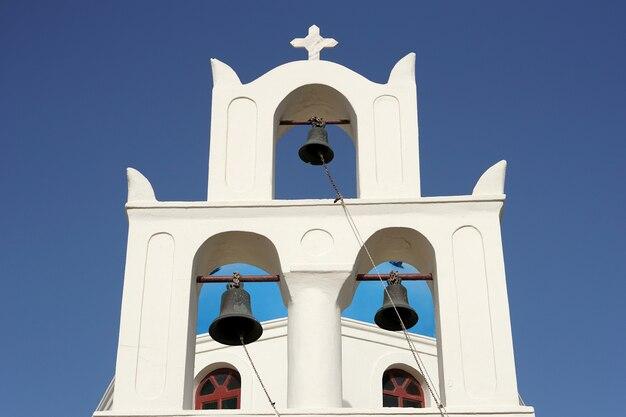 Église blanche avec des cloches sous un ciel bleu à santorin, grèce