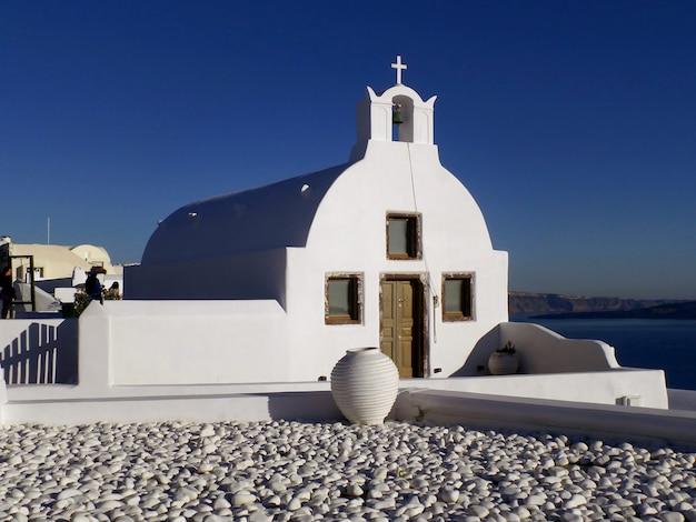Église blanche de style des îles grecques contre le ciel bleu ensoleillé, village d'oia, île de santorin, grèce