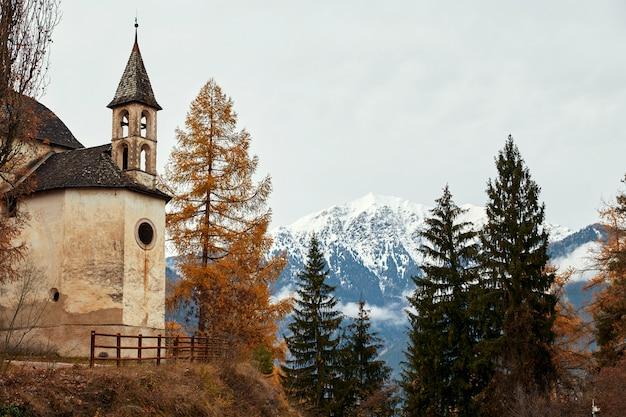 Église et forêt d'automne colorée avec des montagnes
