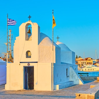 Église grecque orthodoxe d'agios nikolaos dans le port de la ville d'égine au coucher du soleil, grèce