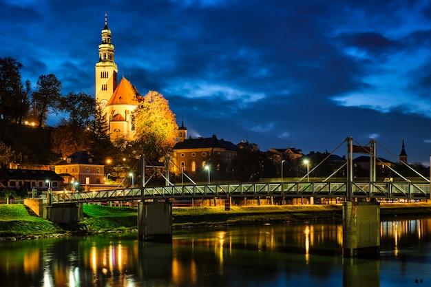 L'église leprosenhauskirche et le pont mullner steg illuminés la nuit. salzbourg, autriche