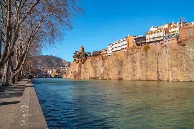 Église et maisons de metekhi au bord d'une falaise au-dessus de la rivière kura. tbilissi, le centre-ville historique