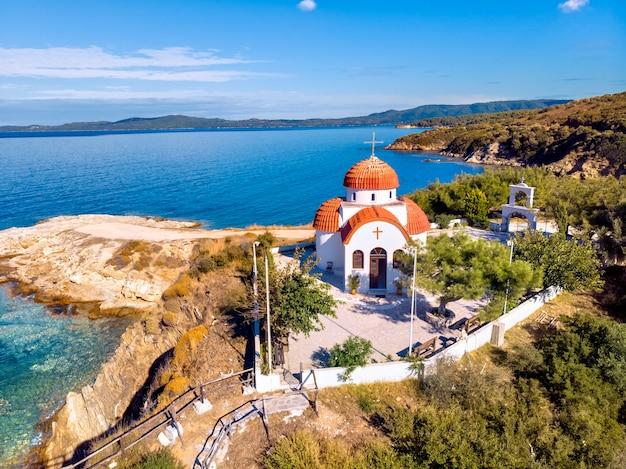 Église et mer avec plage et montagnes à nea roda, halkidiki, grèce