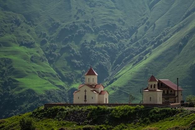 Église sur une montagne en géorgie. une journée d'été ensoleillée dans les montagnes du caucase