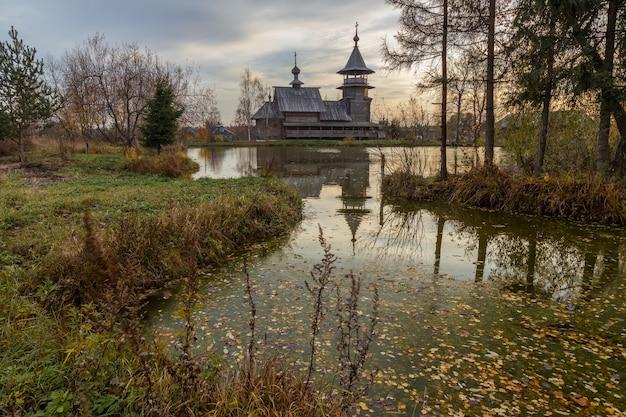 Église orthodoxe en bois de l'annonciation et son reflet dans le lac un jour d'automne. région de moscou, district de sergiev posad. le village de blagoveshheniye