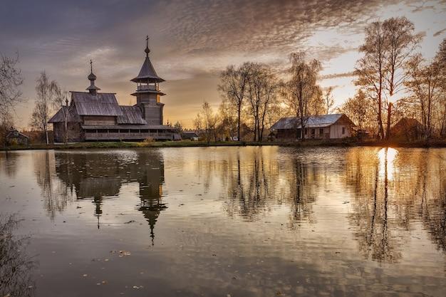 Église orthodoxe en bois de l'annonciation et son reflet dans le lac un jour d'automne, sergiyev posad. le village de blagovescheniye
