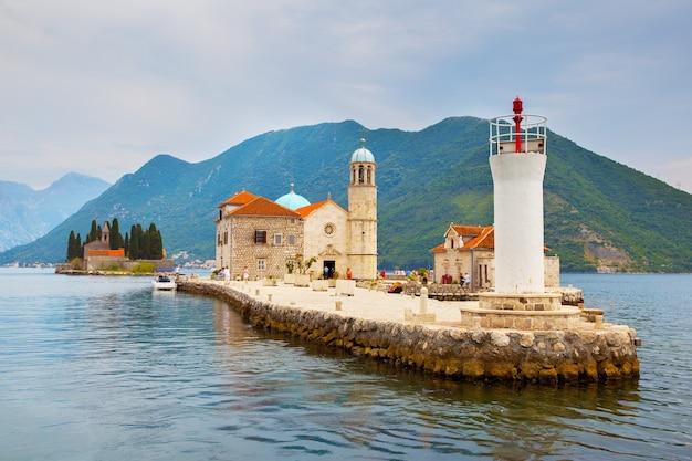 Église et phare de notre-dame des roches sur une petite île de la baie de kotor près de la ville de perast, monténégro