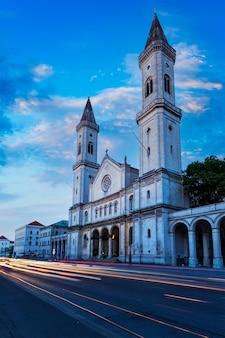 Eglise saint-ludwig (ludwigskirche) dans la soirée. la lumière de la voiture trace le flou de mouvement en raison d'une longue exposition. munich, allemagne