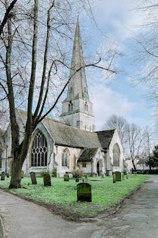Église sainte-marie sur une pelouse verte entourée de tombes et d'arbres