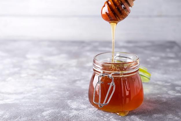 Égouttement de miel en pot sur la table