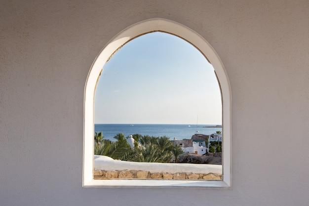 Egypte. un regard à travers le cadre sur les palmiers. belle vue. maison blanche et véranda avec vue sur la mer et les palmiers. vue mer depuis la chambre