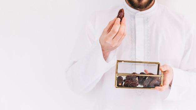 Eid al-fitr concept avec homme tenant la boîte de dates