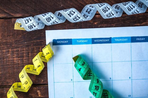Élaborer et planifier un programme d'entraînement sportif et de régime. sports et mode de vie sain. un ruban à mesurer. motivation. concept sport et régime