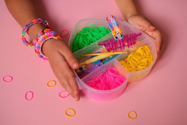 Des élastiques pour tisser des bracelets en boîte sont tenus par un enfant.